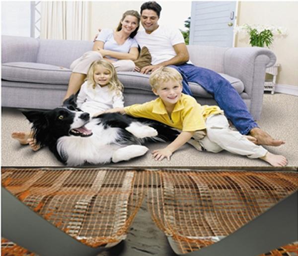 Четиричленно семейство седящо на диван и килим отопляващо се с подово отопление на ток