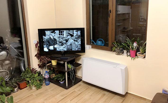 Воден конвектор за отопление и охлаждане монтиран на стена в хол до телевизор