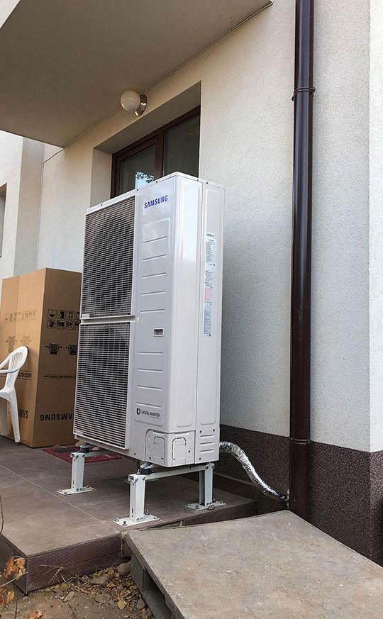 Външно тяло на термопомпа въздух вода SAMSUNG 16kW, монтирано върху стойки пред къща